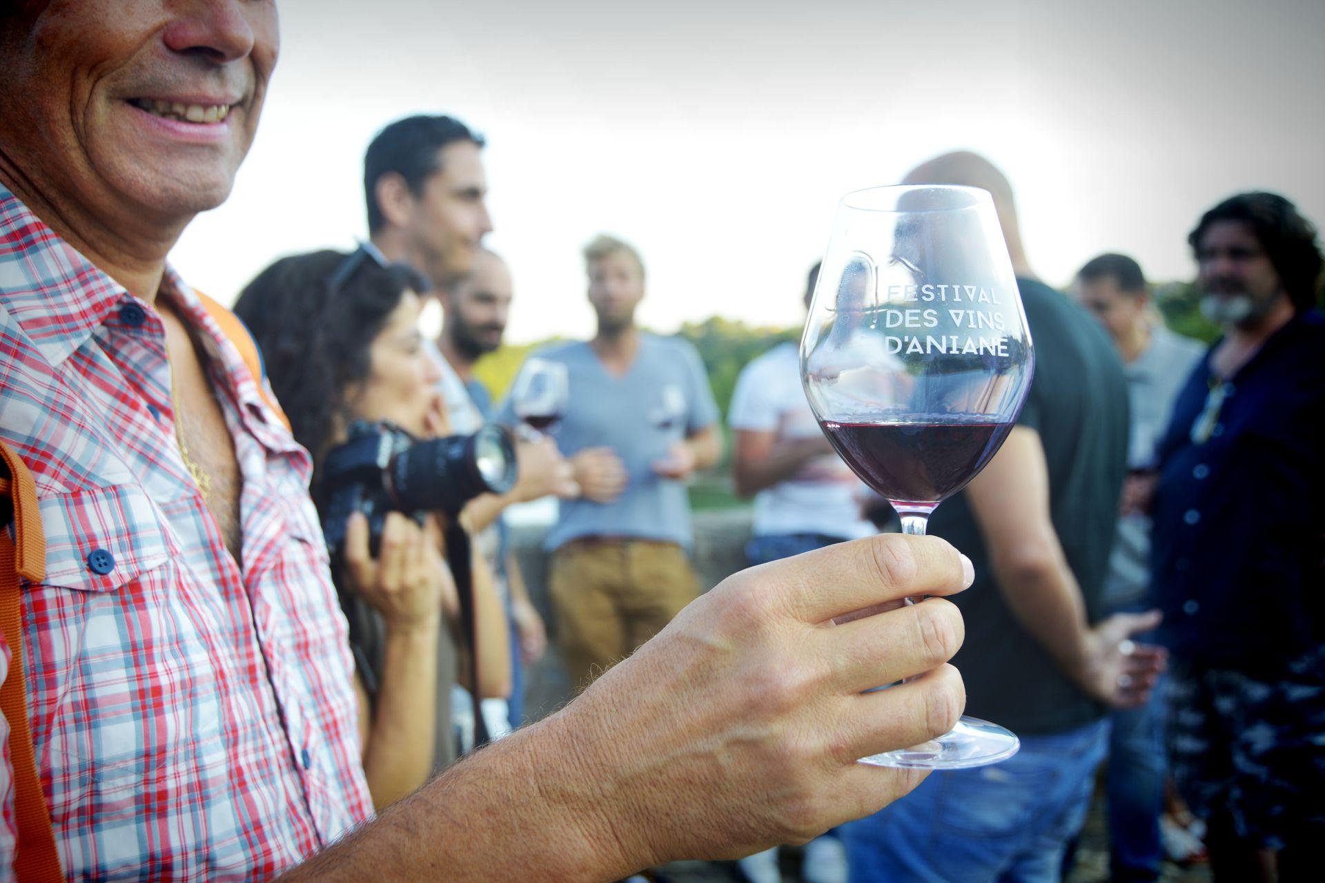 Festival des vins d'Aniane avec un verre de vin rouge au premier plan