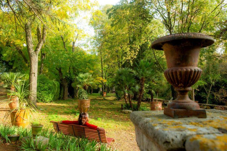 Aniane, jardin du Domaine de Rieussec, jeunior, de dos assise sur un banc