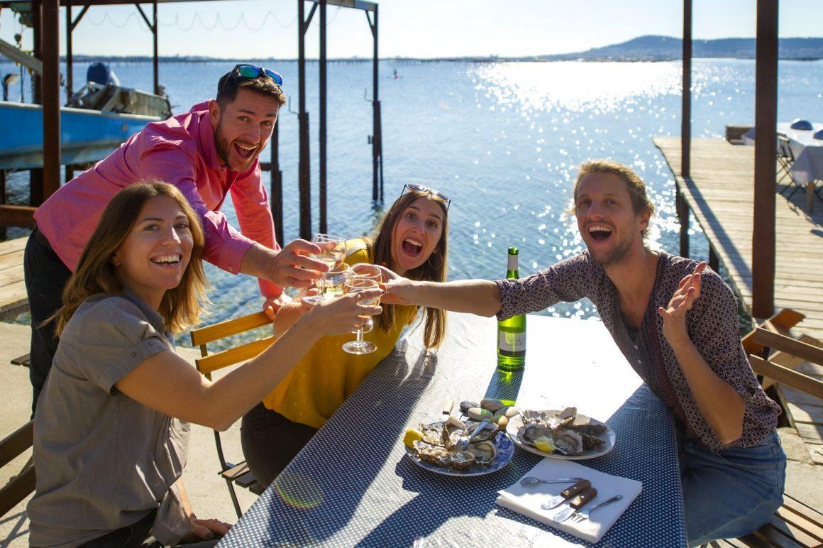 Tribu de jeunes en train de boire un verre de vin et manger des huîtres au Petit Mas Loupian, au bord de l'Etang de Thau ©D.Cavailhes
