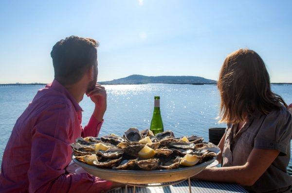 Couple de jeunes en train de boire un verre de vin et manger des huîtres au Petit Mas Loupian, au bord de l'Etang de Thau ©D.Cavailhes