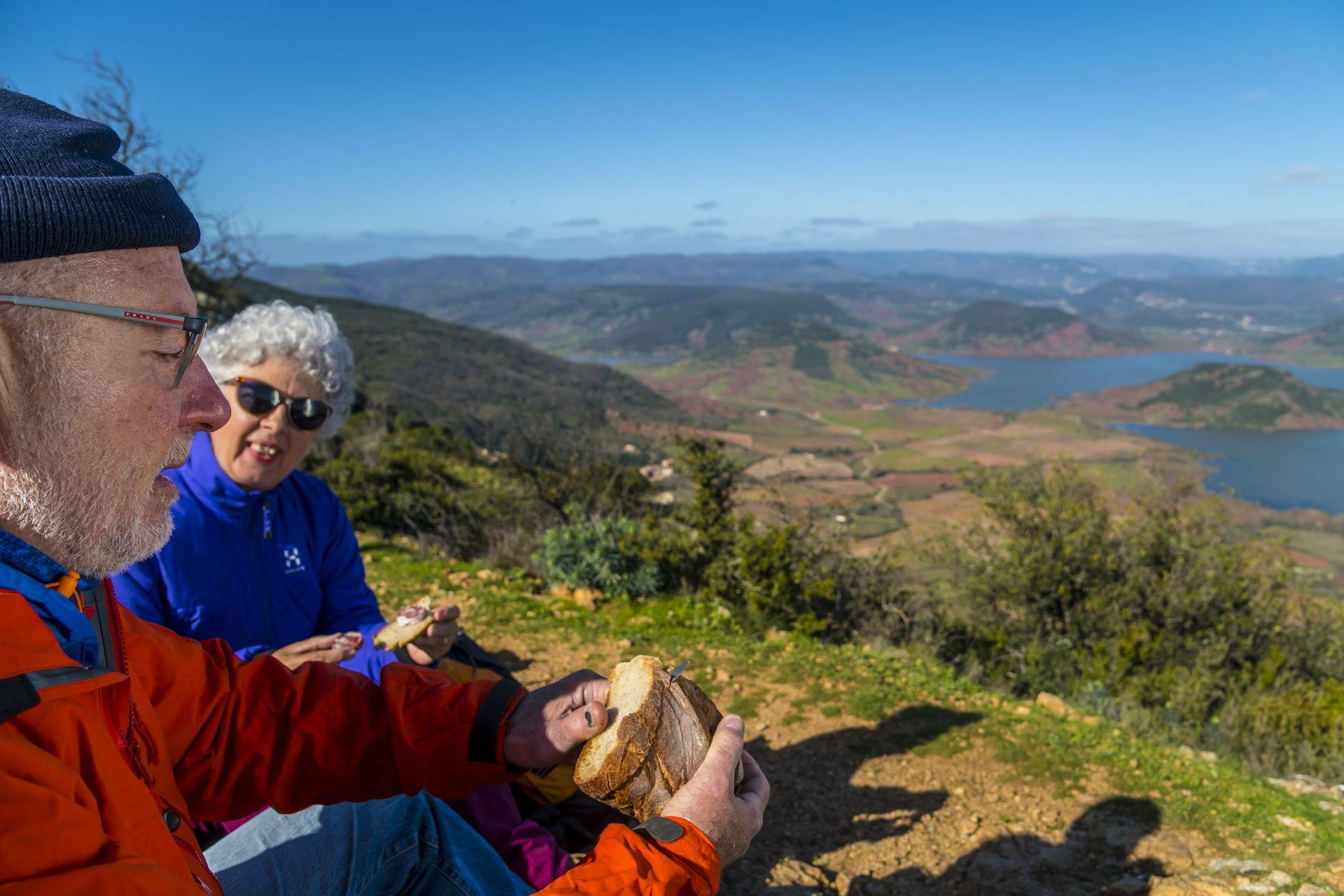 Couple de seniors qui pique-nique en haut du Mont Liausson, vue sur le lac du Salagou