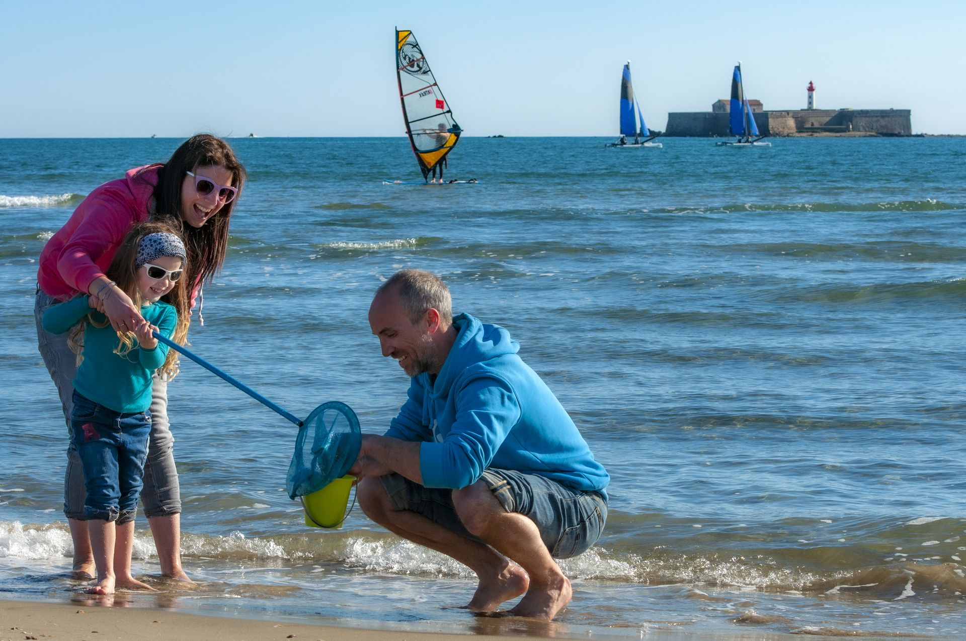 Une famille avec un enfant, en train de ramasser des crabes au bord de la mer, devant le fort Brescou au Cap d'Agde