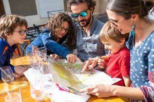 Famille en terrasse au restaurant Terrasse Mimosa Montpeyroux regardant une carte touristique
