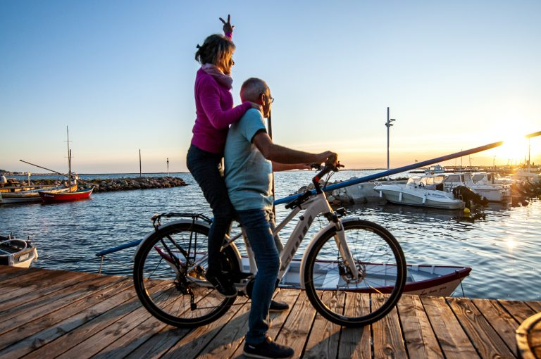 Un couple quinca jeuniors à vélo observent le coucher du soleil sur le port de Bouzigues au bord de l'étang de Thau