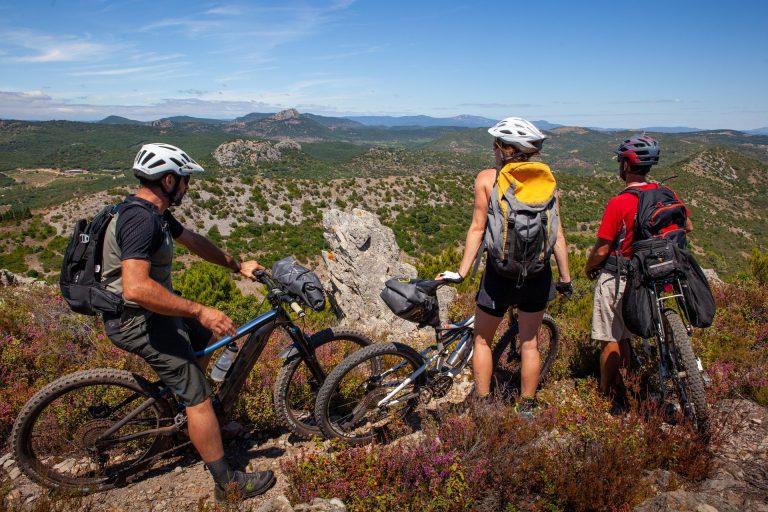 3 vététistes admirent le paysage sur les hauteurs de Cabrières