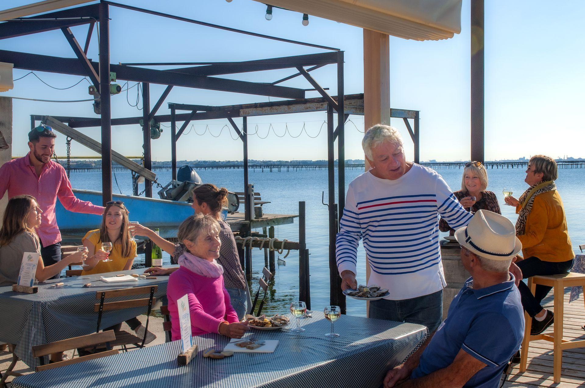 Un couple quincas déguste des huîtres de Bouzigues au Petit Mas de Loupian