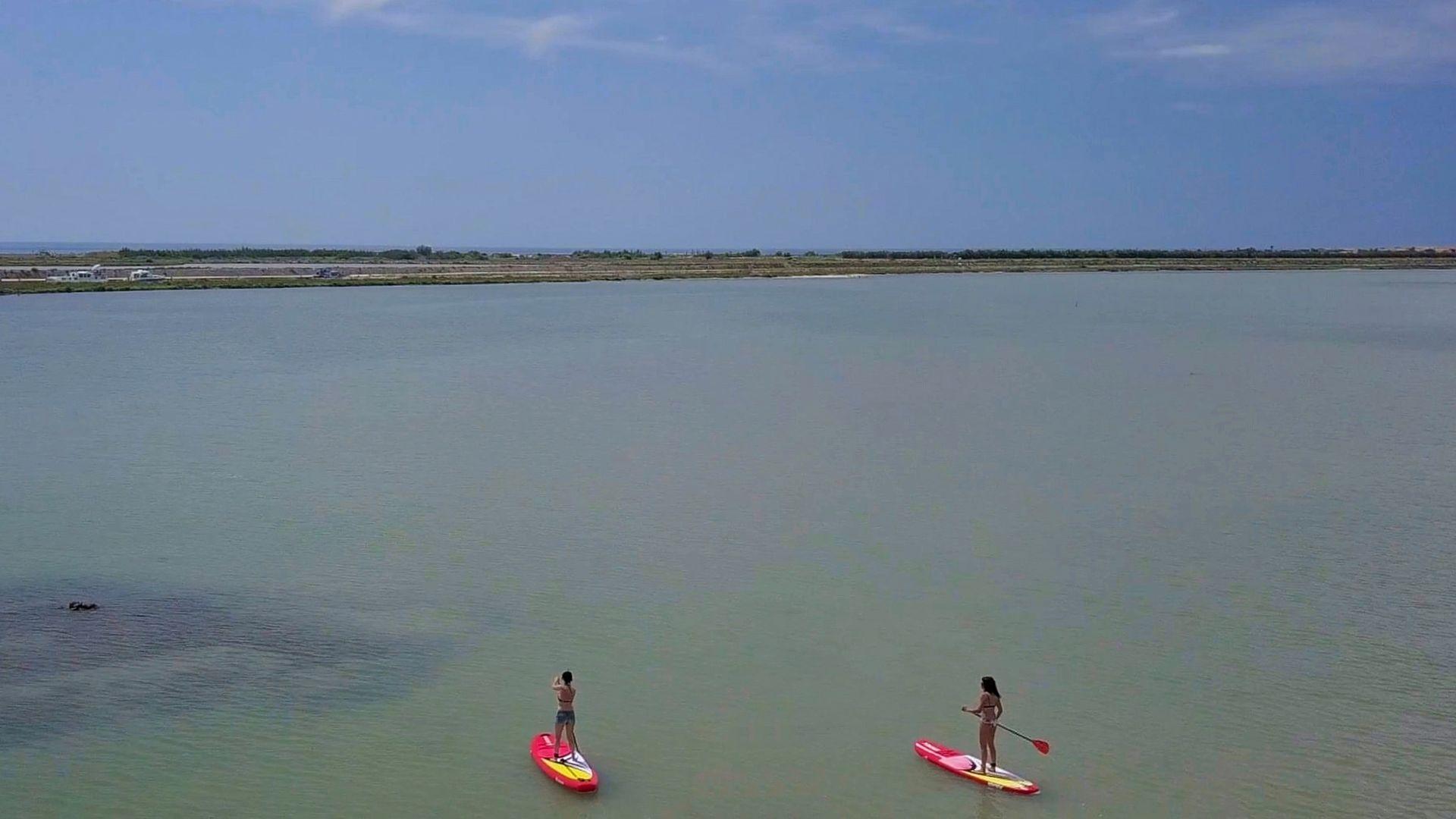 2 jeunes femmes font du paddle sur l'étang de Thau