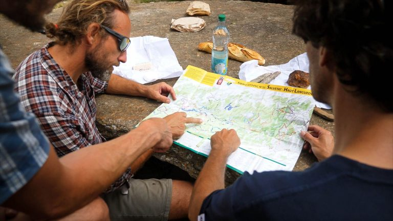 des vététistes regardent une carte de parcours pendant leur pique-nique