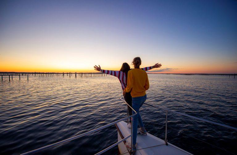 Un couple de jeunes en train de regarder le coucher du soleil sur l'étang de Thau sur un bateau-catamaran, devant les parcs à huîtres et Sète en toile de fond