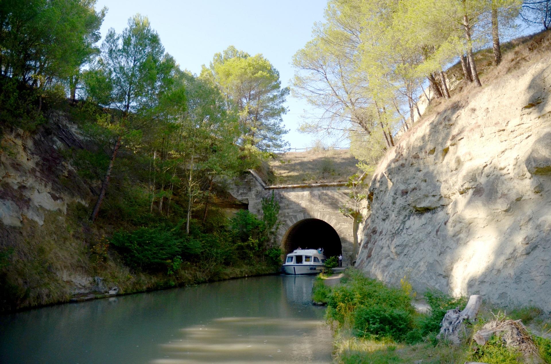 Bateau sur le Canal du Midi qui sort du tunnel du Malpas