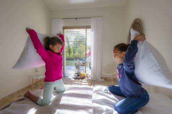Bataille de polochons entre enfants, 2 petites filles dans une chambre