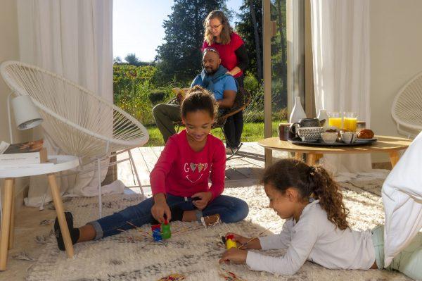 Une famille dans une chambre, avec deux enfants qui jouent et les parents qui lisent un livre sur la terrasse ensoleillée, avec en toile de fond les vignes de l'Hérault