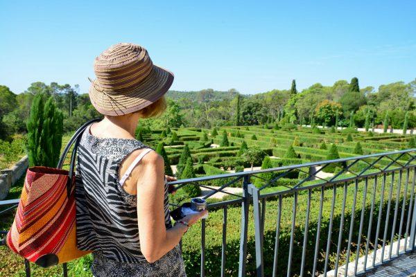 Une femme qui admire le jardin à la française du château auDomaine départemental de Restinclières