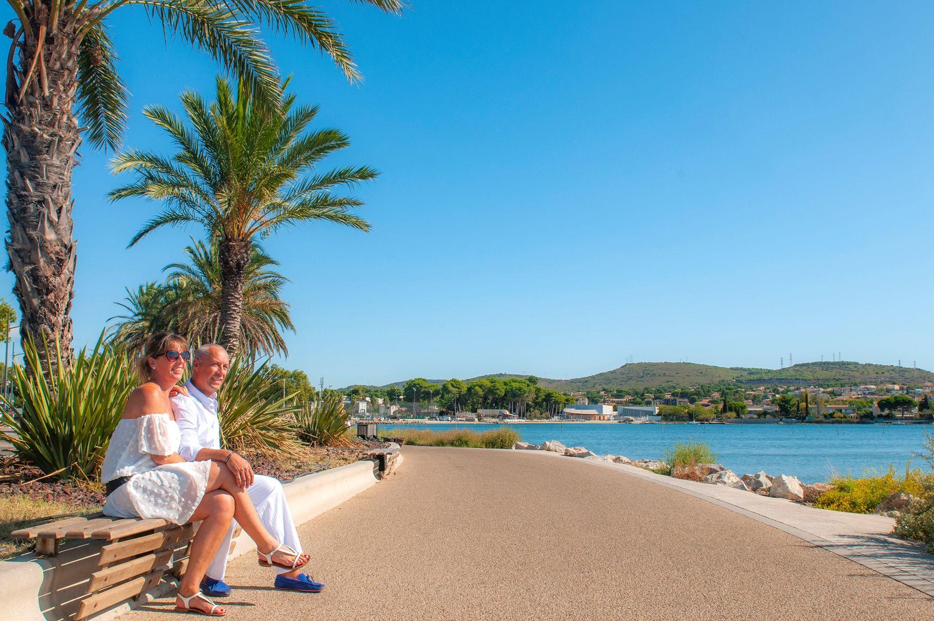 Couple assis sur la promenade Spinosi à Balaruc face à l'étang de Thau