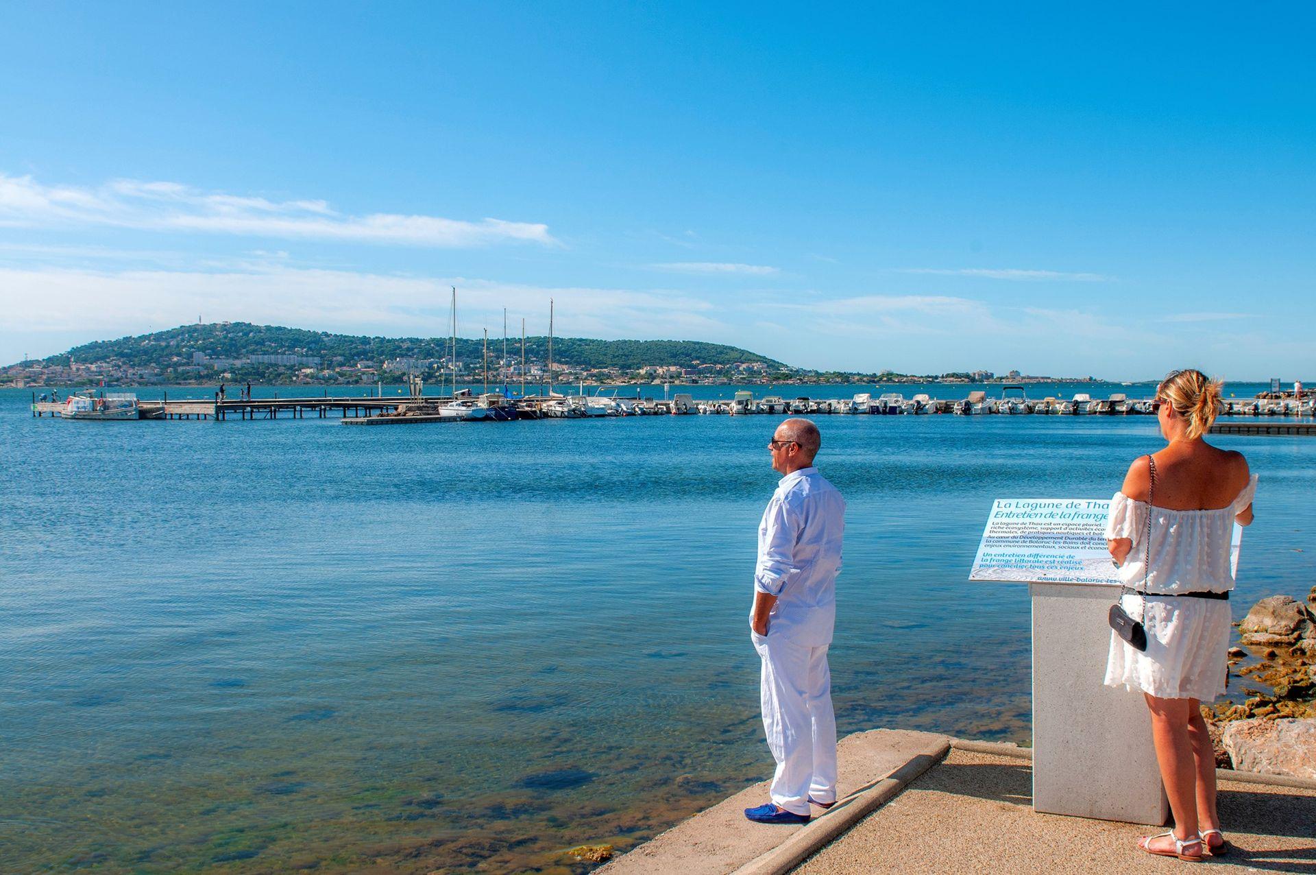 De la promenade Spinosi, un homme regarde l'étang vers Sète