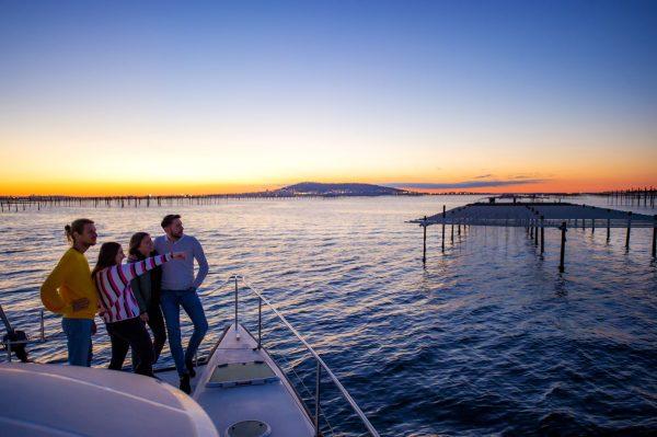 Un groupe de jeunes sur un bateau-catamaran en train de regarder le coucher du soleil sur l'étang de Thau, devant les parcs à huîtres et Sète en toile de fond