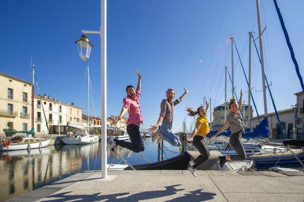 Un bande d'amis de jeunes, en train de faire les fous et de sauter, sur le quai, au bord du Canal à Marseillan