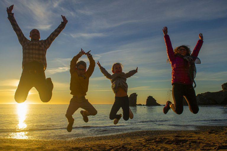 Une famille avec deux enfants qui s'amusent et qui sautent sur la plage au coucher du soleil
