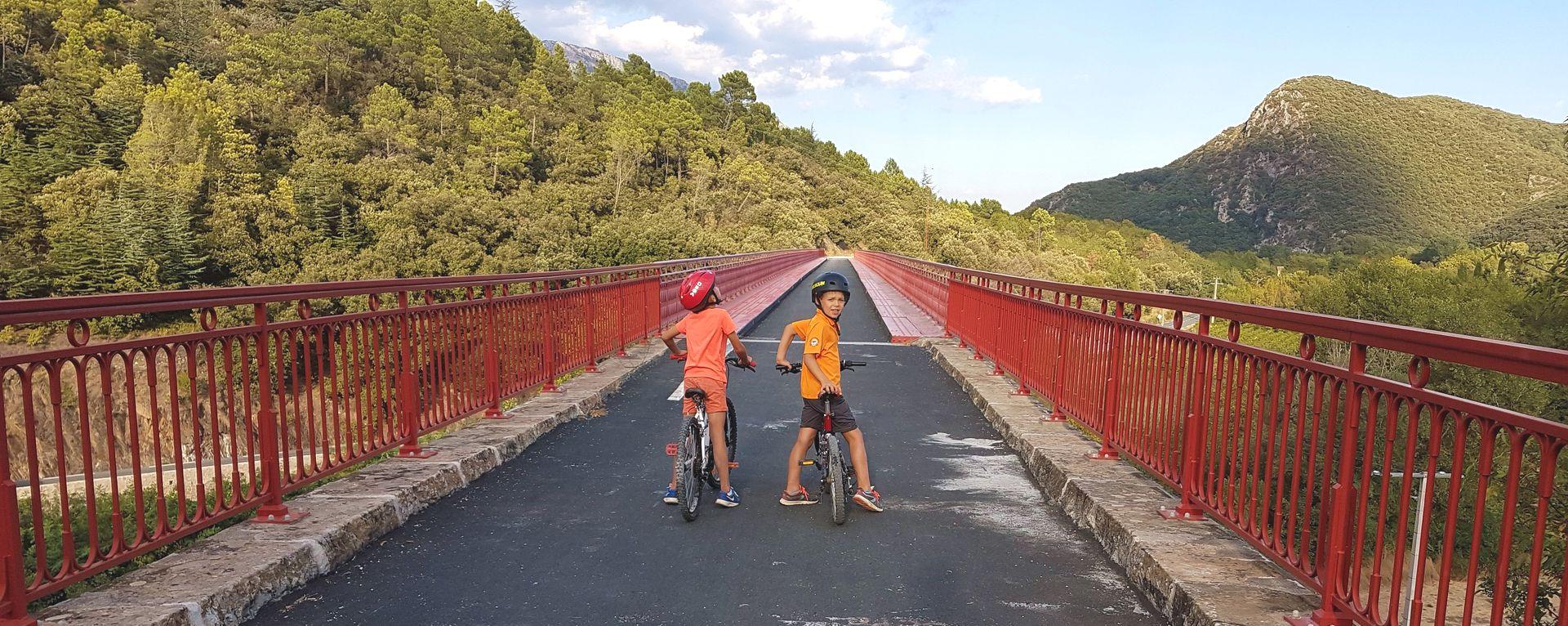Enfants à vélo sur le pont type Eiffel d'Olargues