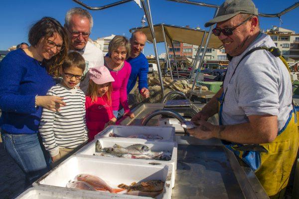 Famille qui achète du poisson à un pêcheur sur le port du Cap d'Agde