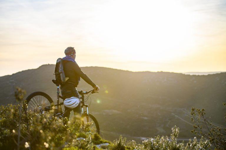 Une homme quicados qui fait une pause en VTT lors d'une randonnée au Puech des Mourgues pour admirer le coucher du soleil