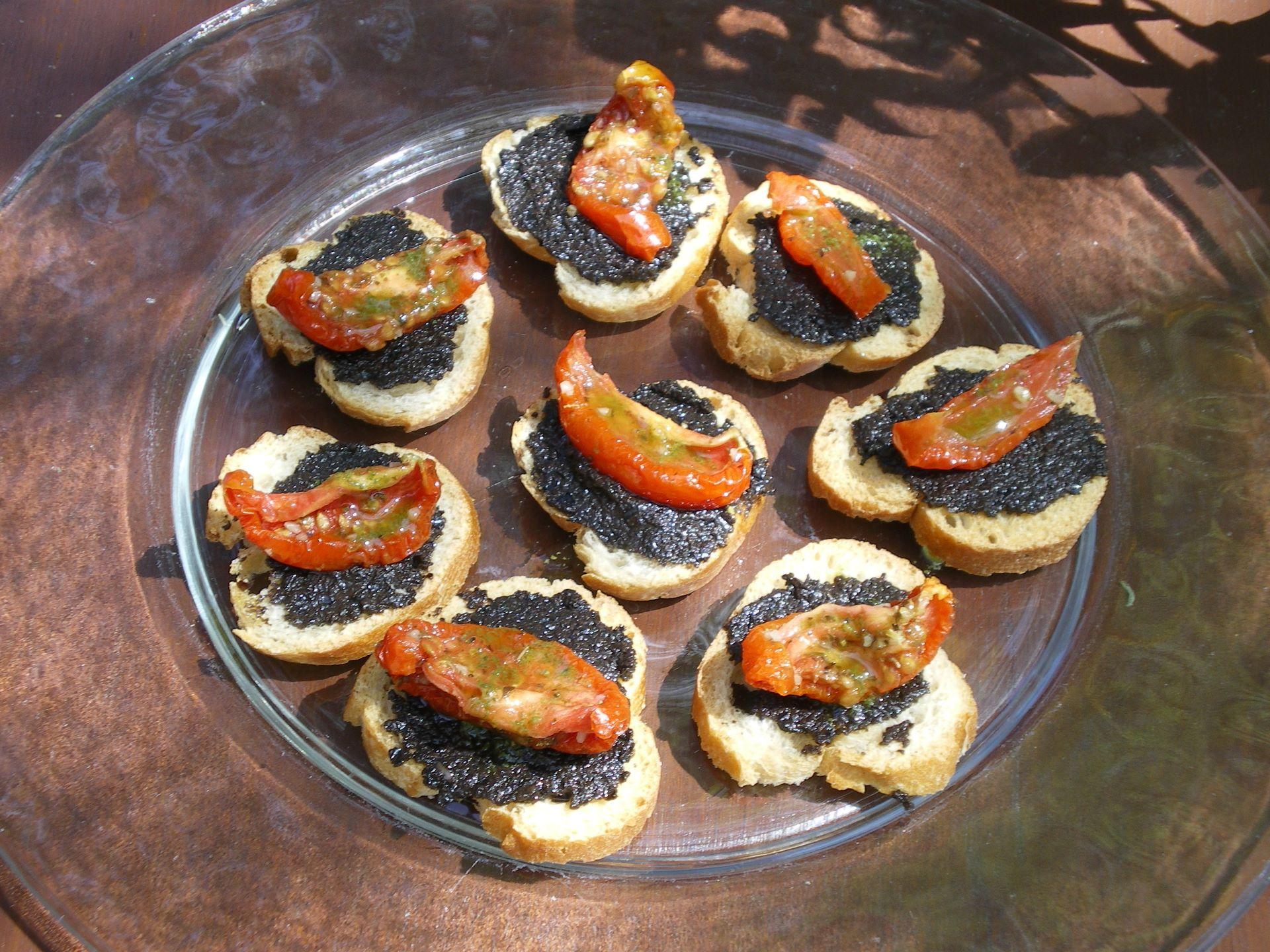 Assiette avec tartines de tapenade d'olives noires et morceaux de tomates séchées