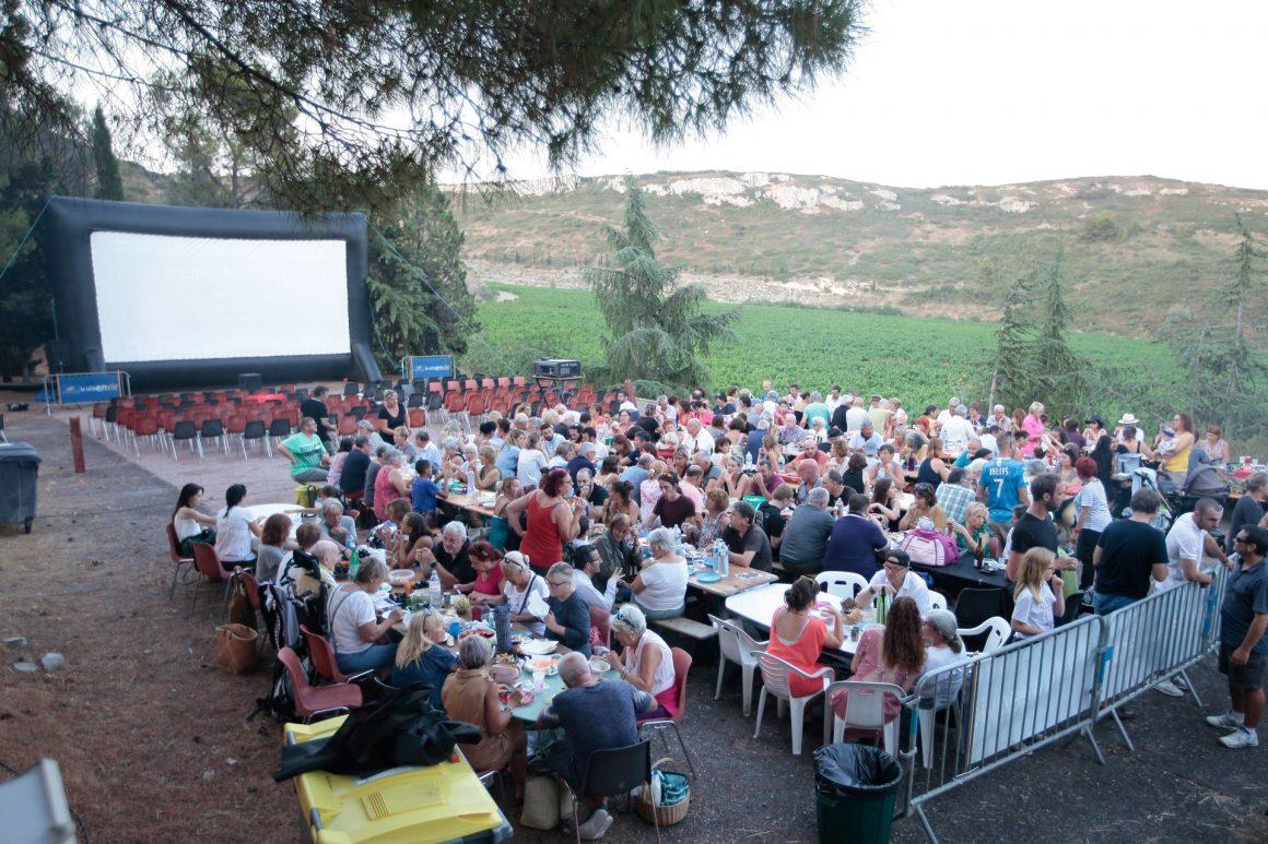 Projection de film au Festival Emmuscades au Mas Rimbaud à Frontignan avec de nombreuses personnes attablées et des vignes en arrière-plan