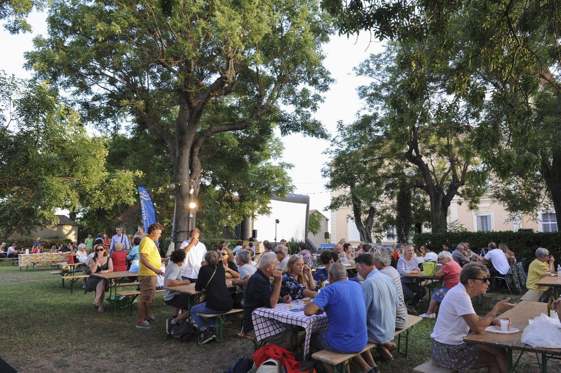 Personnes attablées lors du Festival Emmuscades sour les arbres du Château Lapeyrade à Frontignan, toile de cinéma en arrière-plan