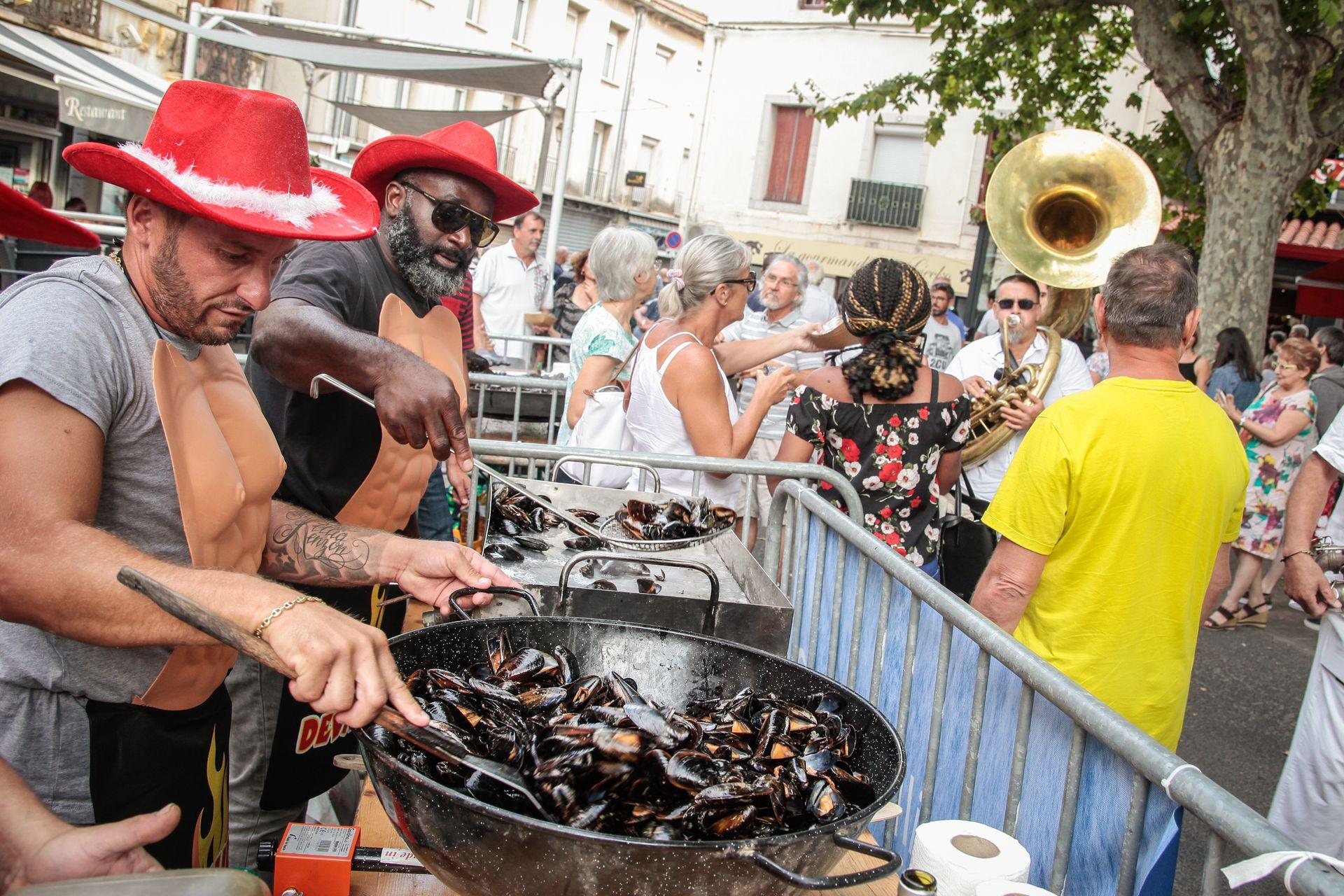2 hommes qui cuisinent des moules dans une grande marmite lors du Festival de brasucade de Moules Total Musclum à Frontignan avec en arrière-plan une fanfare et des personnes qui profitent de l'ambiance