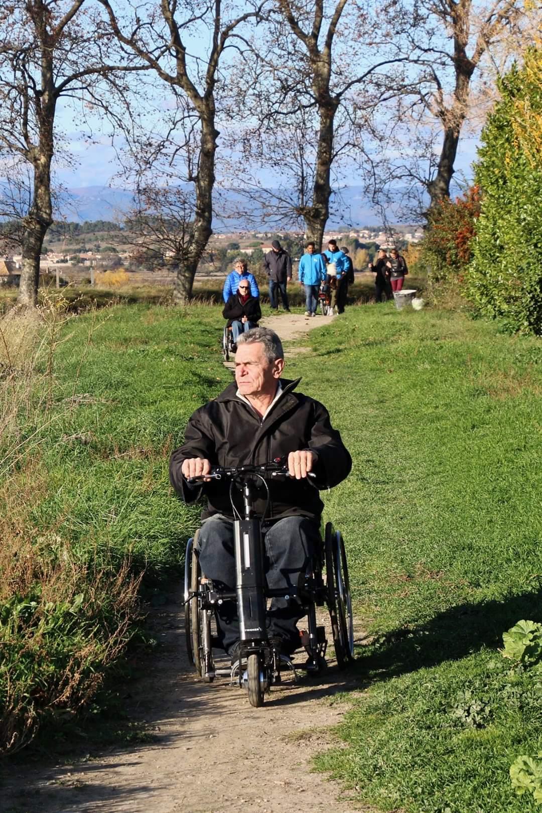 Homme sur un fauteuil avec une 3ème roue électrique