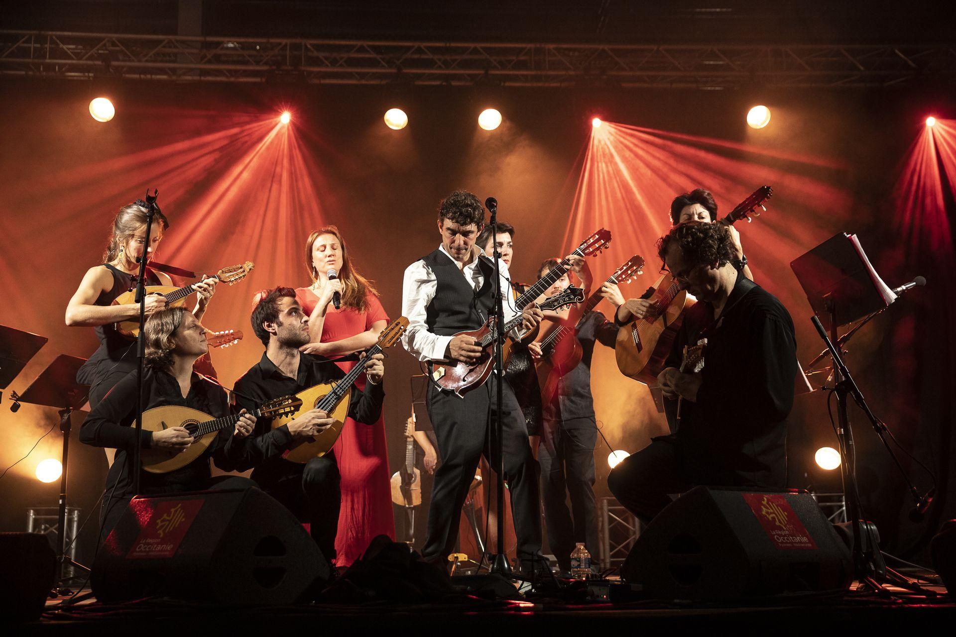 Feloche et musiciens en train de jouer de la guitare et autres instruments à cordes sur la scène de l'Opéra à Montpellier dans le cadre des Internationales de la Guitare Sud de France