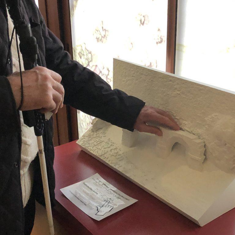 Une personne touche la sculpture du pont d'Ambroix à Ambrussum