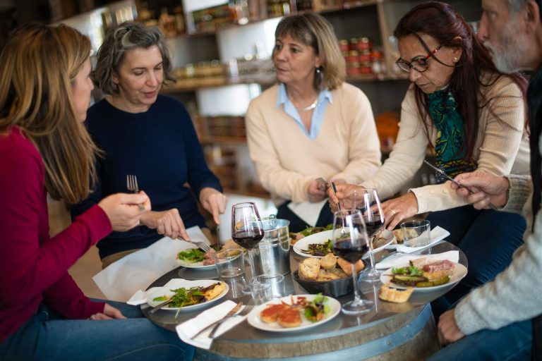 Une tribu, un groupe de copines en train de manger dans un restaurant