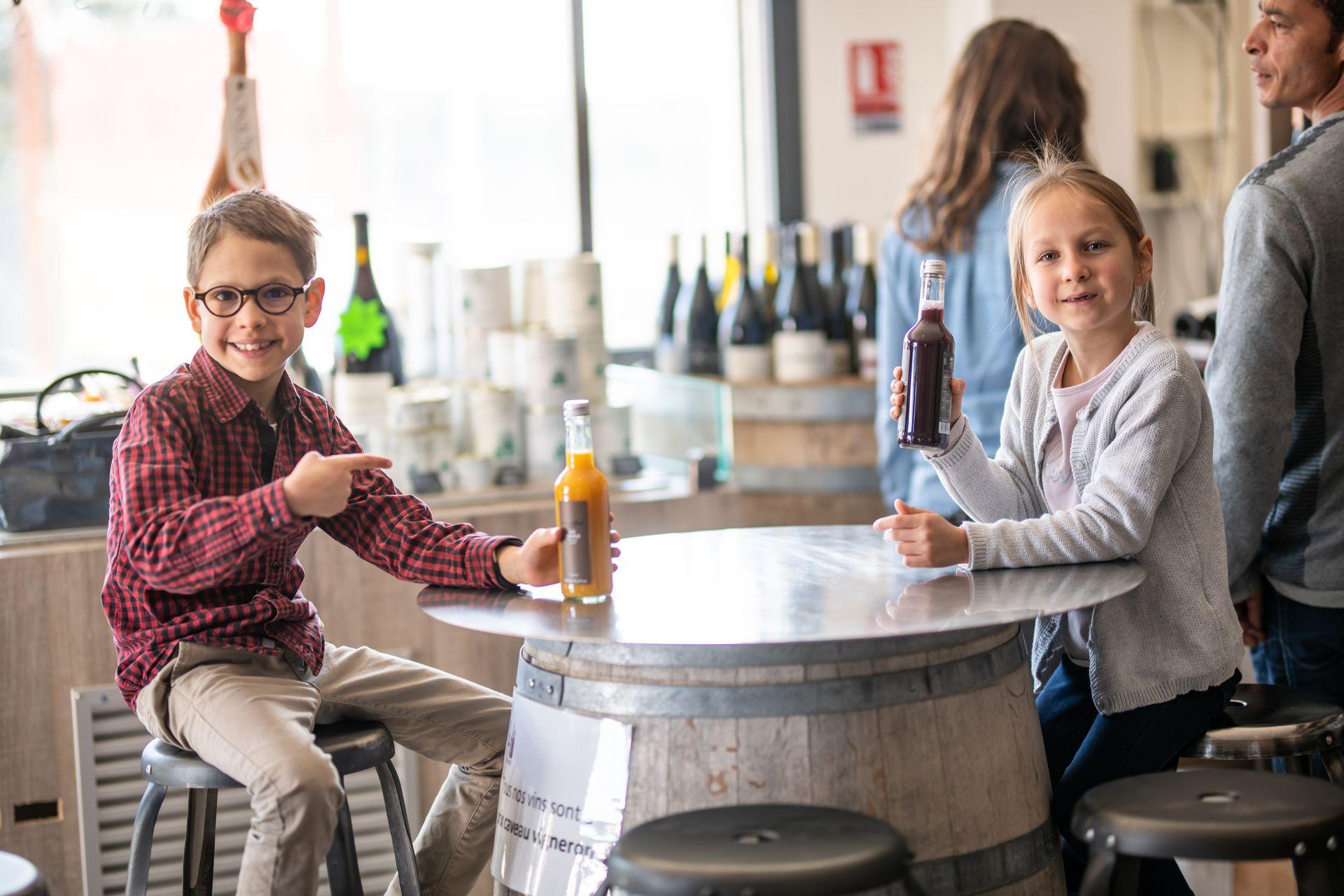 Des enfants buvant du jus de fruit assis sur une table, dans la boutique Invinaterra à Sauteyrargues
