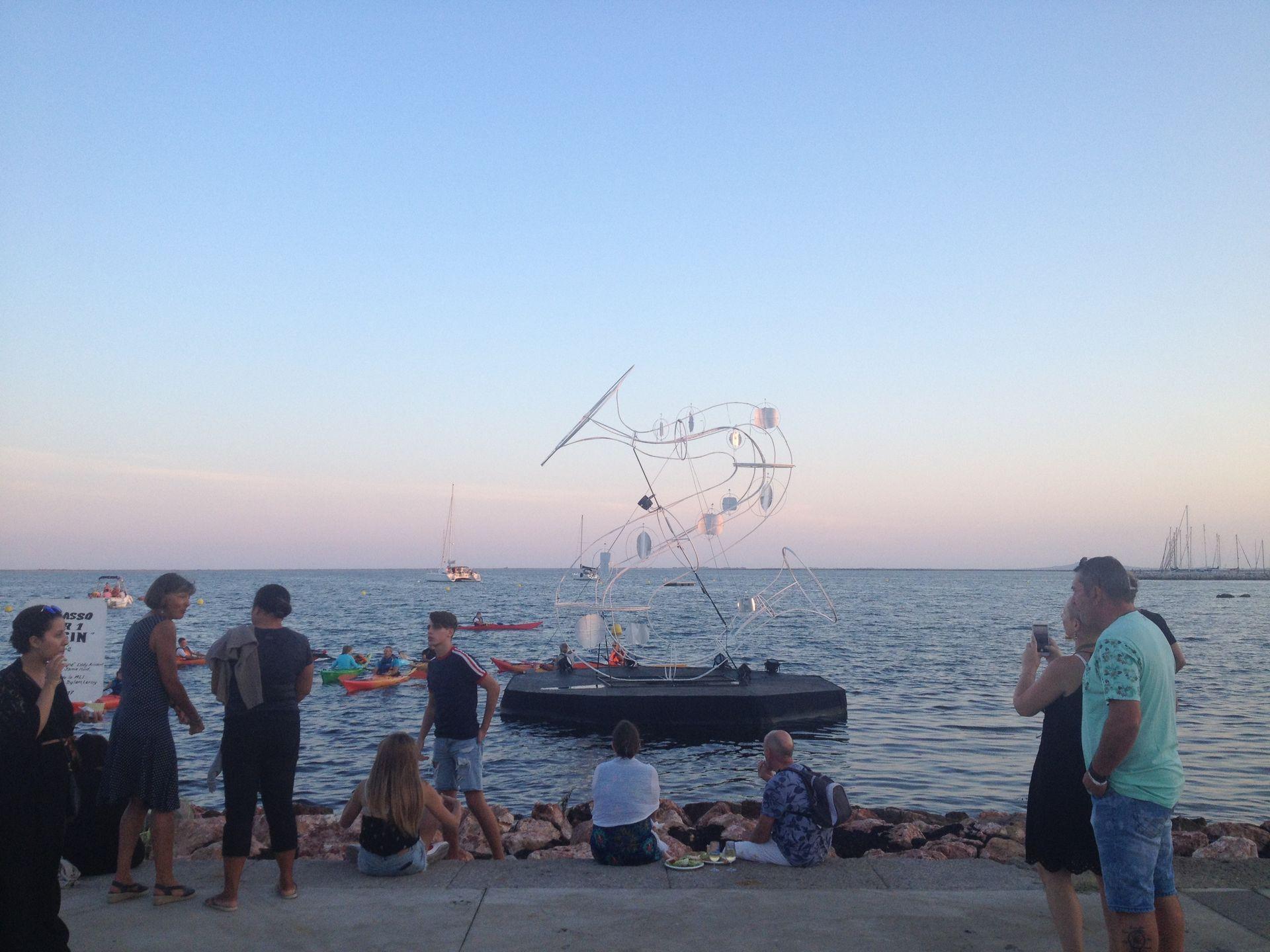 Structure flottante, canoë et bateaux sur l'étang de Thau - personnes assises sur la digue de rocher lors du Festival de Thau à Mèze