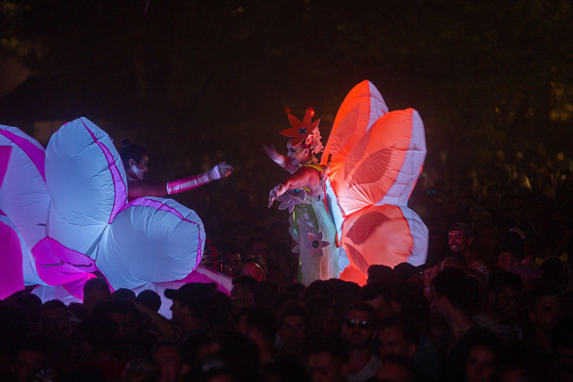 Personnes déguisées en fleurs fluorescentes sur échasses au milieu de festivaliers qui dansent à la nuit tombée lors de la Family Piknik au Domaine de Grandmont à Montpellier