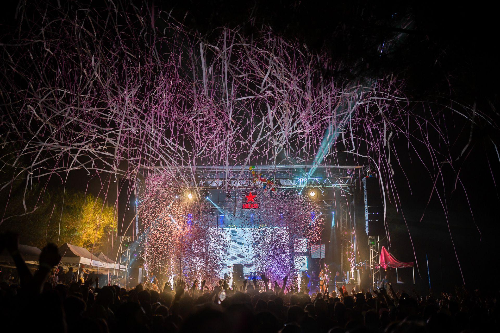Pluie de cotillons et confettis roses au-dessus de festivaliers qui dansent devant la scène de la Family Piknik à la nuit tombée