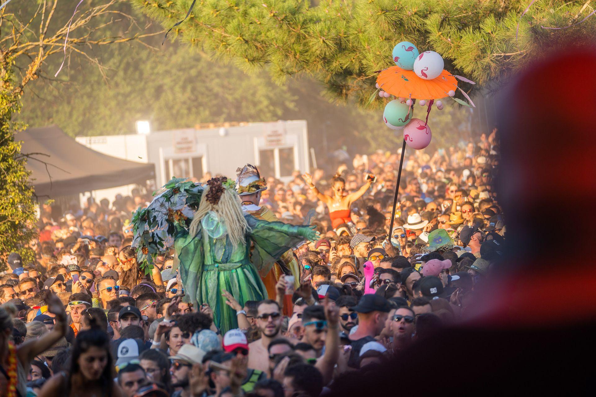 Festivaliers et personnes déguisées sur échasses en train de danser en journée au Domaine de Grandmont à Montpellier dans le cadre de la Family Piknik