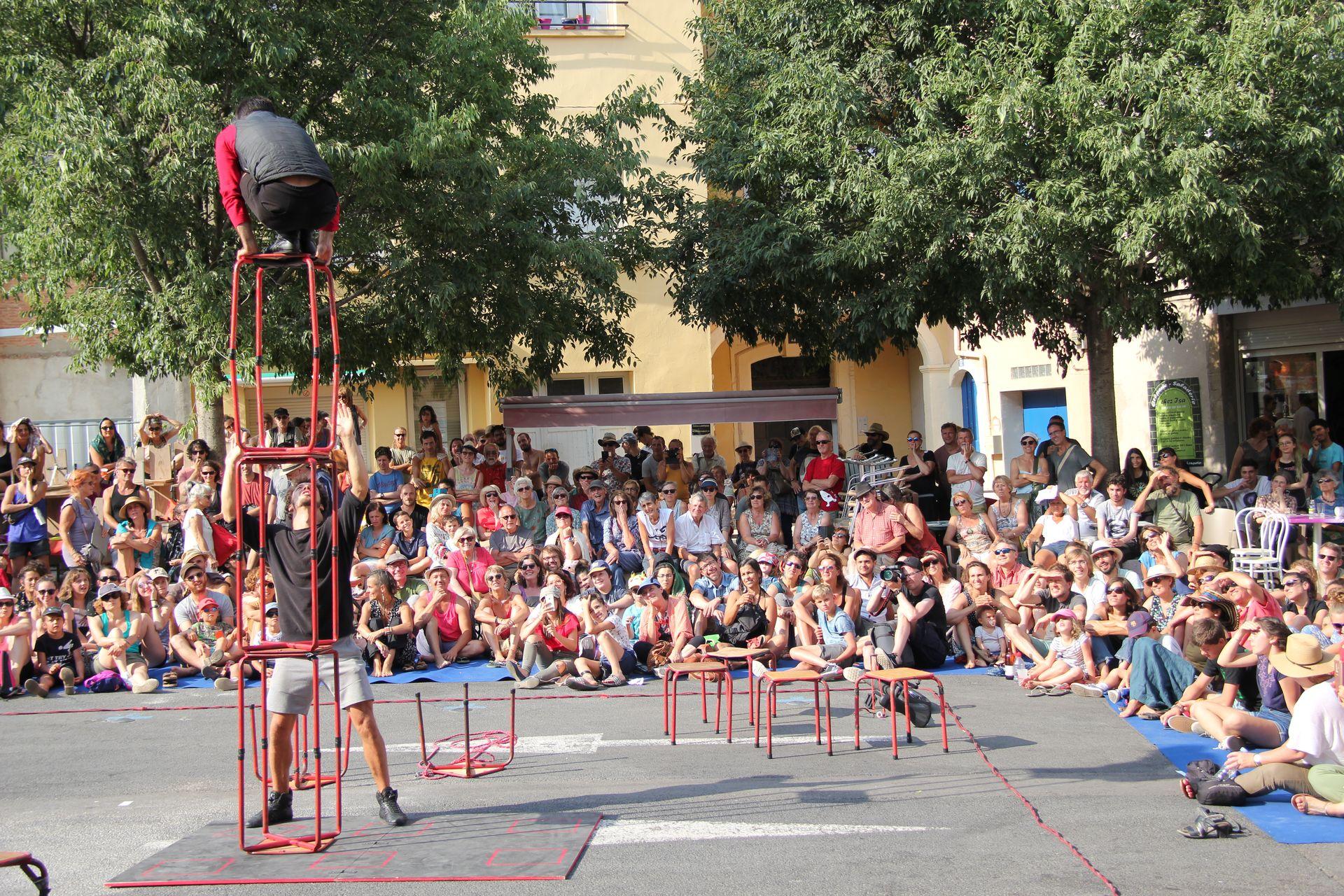 Duo d'acrobates du cirque Bankal faisant un spectacle de rue à Lodève devant une foule de visiteurs en famille dans le cadre du Festival Résurgence en été