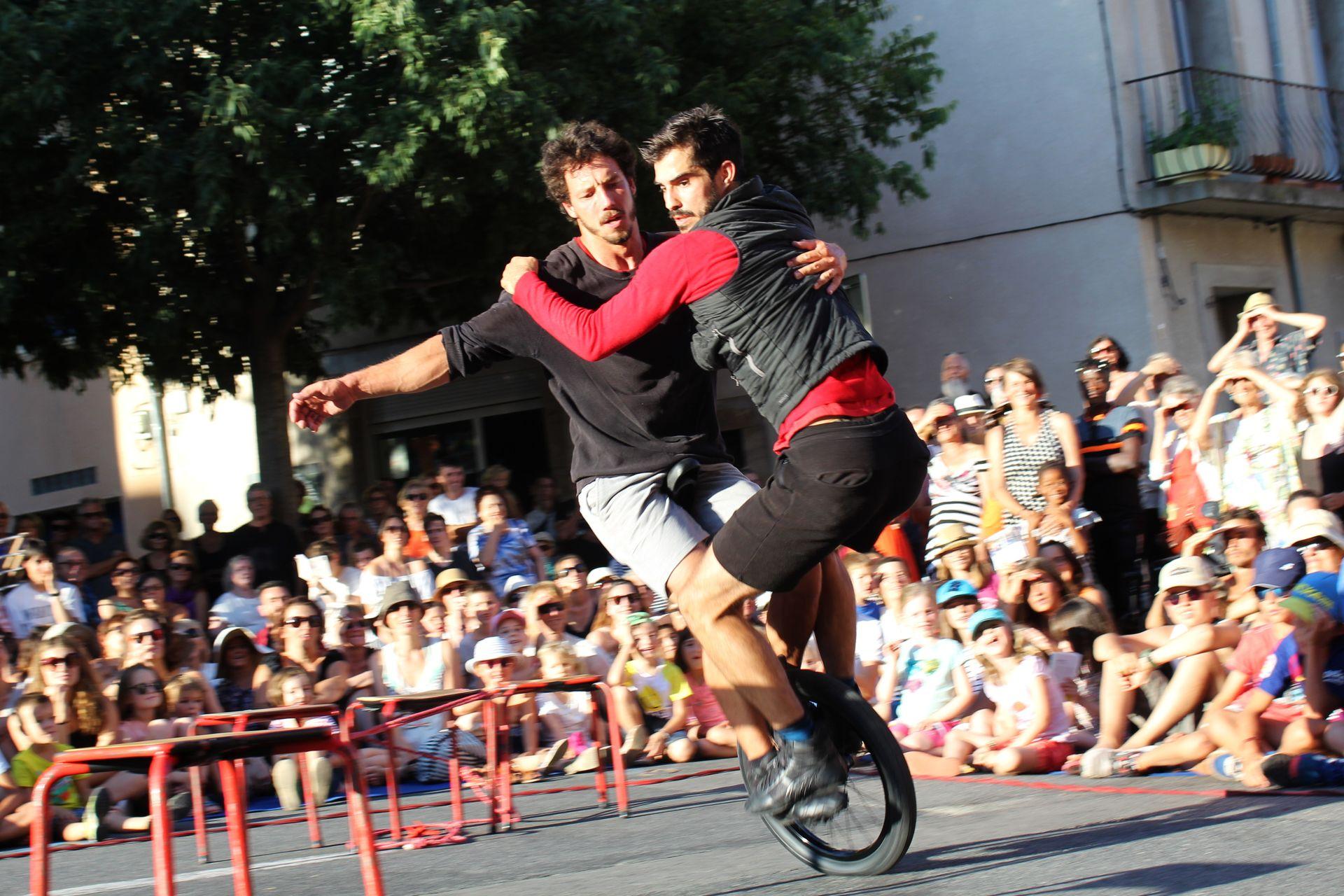 Duo d'acrobates du cirque Bankal en train de pédaler sur une même roue devant des spectateurs en famille sur une place de Lodève lors du Festival Résurgence en été