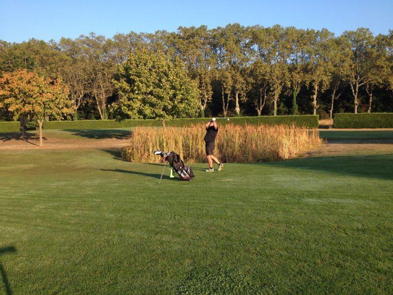 Joueur de golf qui lève son club en l'air prêt à taper dans la balle sur le terrain de golf de Lamalou les Bains