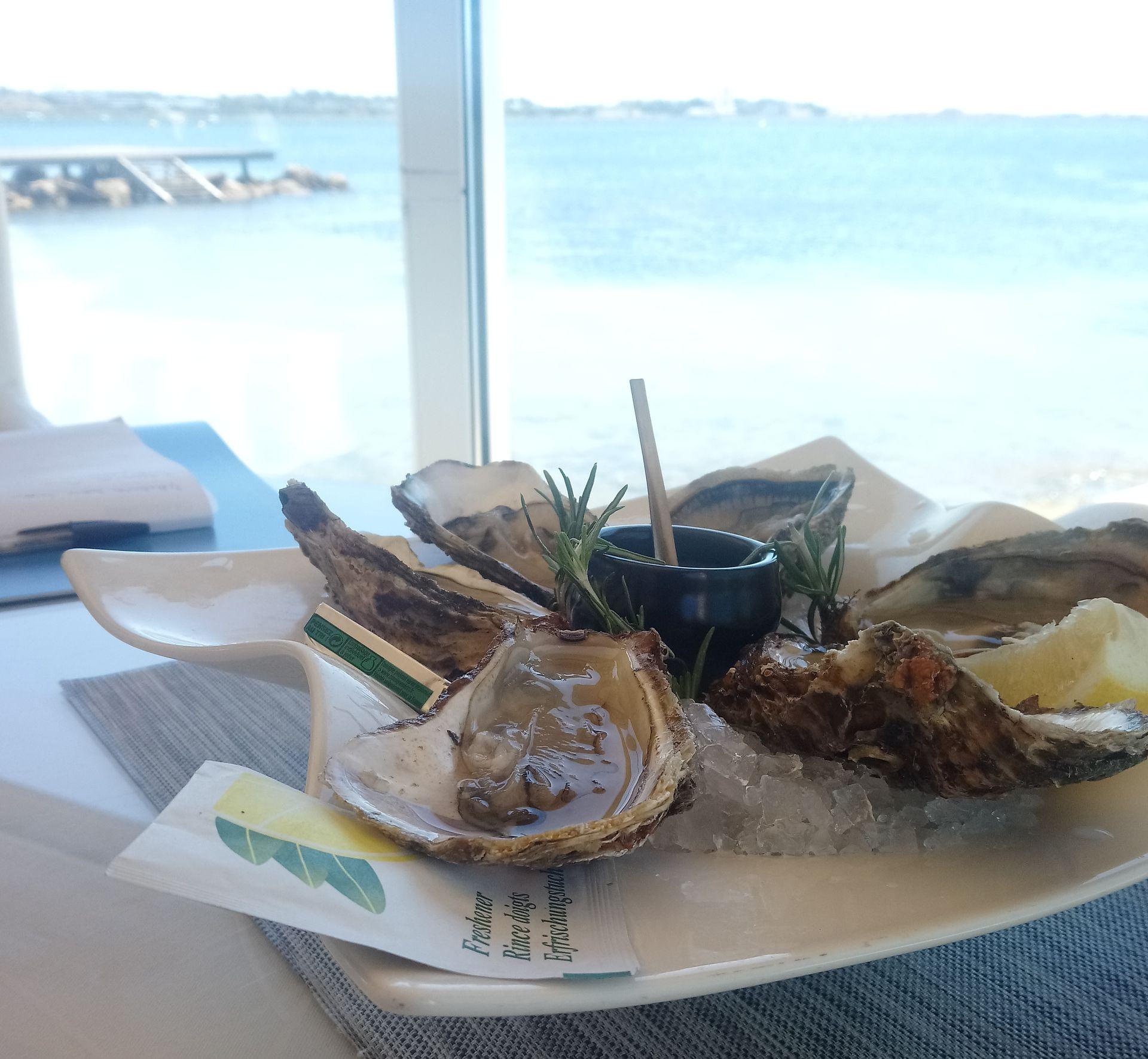 Assiette d'huîtres de Bouzigues au restaurant le Grand Large avec l'étang de Thau en arrière-plan derrières les baies vitrées