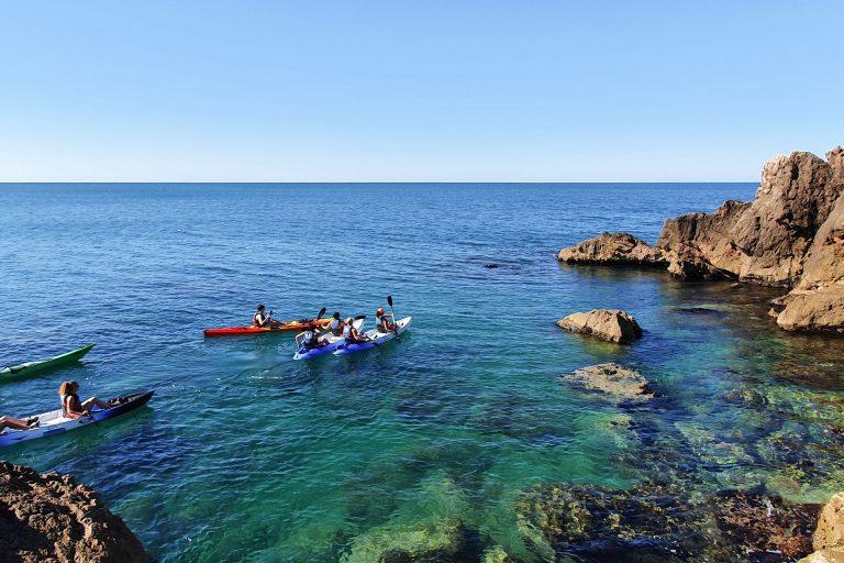 Groupe de personnes en Kayak de mer au pied des falaises de Sète