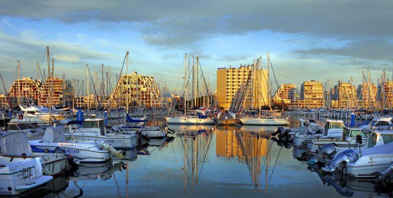 Vue sur le port et les bateaux de La Grande Motte avec le soleil couchant sur les bâtiments en arrière-plan