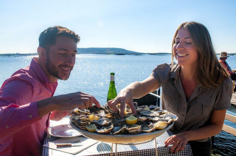 Un couple de jeunes, en train de manger des huîtres dans un mas conchylicoles, le petit Mas à Loupian, avec l'étang de Thau juste à côté
