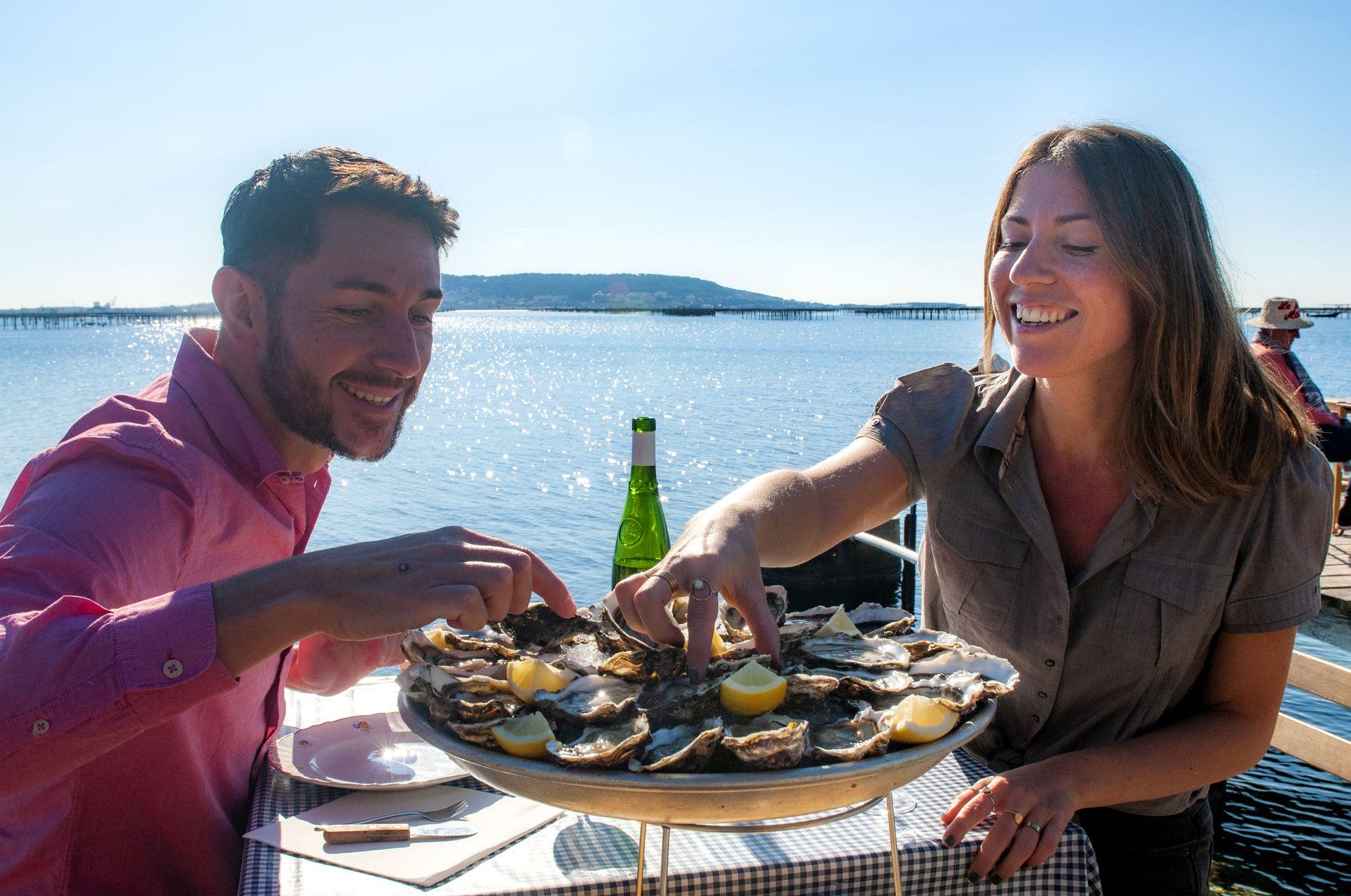 Couple qui déguste un plateau d'huîtres au bord de l'étang de Thau auPetit Mas à Loupian