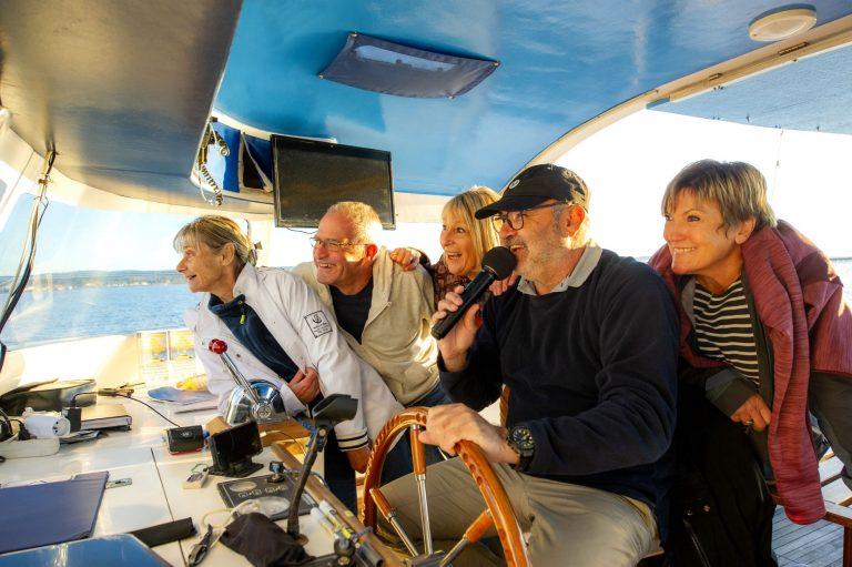 Un groupe d'amis de jeuniors, sur bateau promenade sur l'étang de Thau, en train de rigoler en écoutant le capitaine au micro qui racontent la visite...