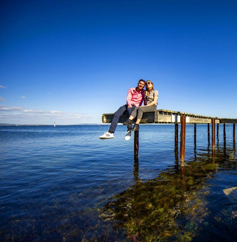 Couple de jeunes assis sur un ponton au dessus de l'étang de Thau