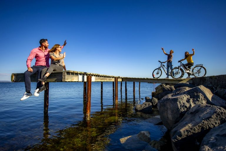Couple de jeunes assis sur un ponton au dessus de l'étang de Thau, faisant signe à un couple de jeunes arrivant en vélo