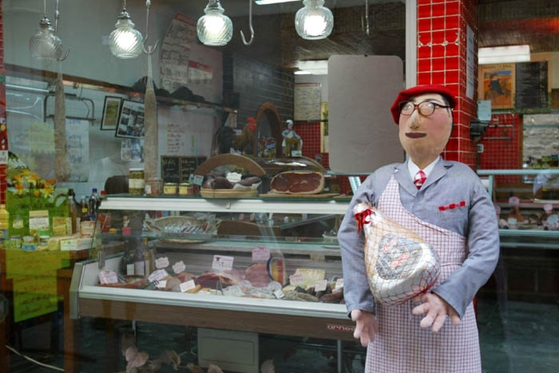 Petetas de Murviel Lès Béziers - Poupée de chiffon à taille humaine représentant un boucher avec tablier et jambon dans les mains devant la boucherie du village